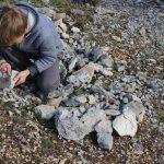 un enfant qui frotte des pierres telles des silex